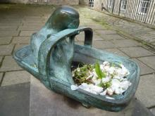 Statue of Parakeet and Garden Trug on plinth in memory of Susannah Alice Stephen